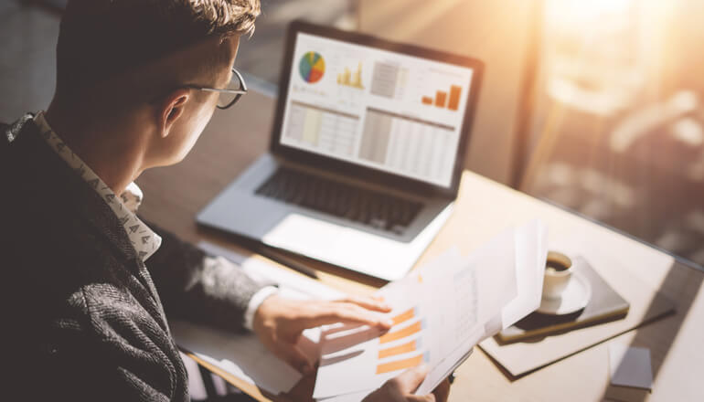 Financial analyst reviews data on laptop computer