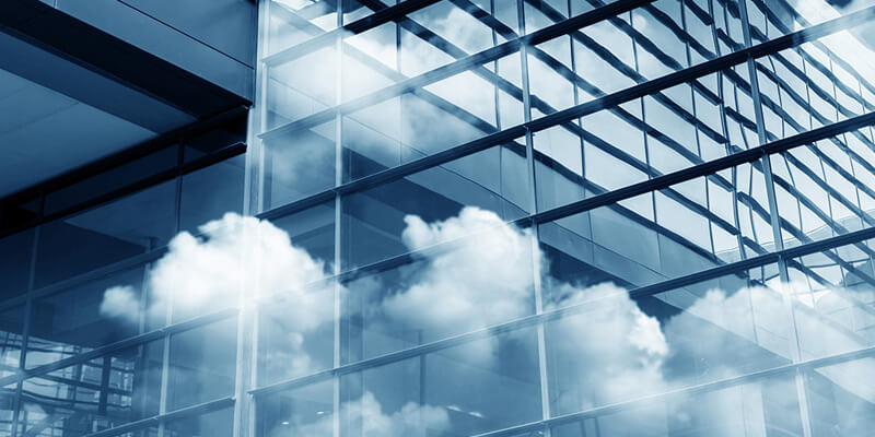 Clouds reflected through modern glass office building