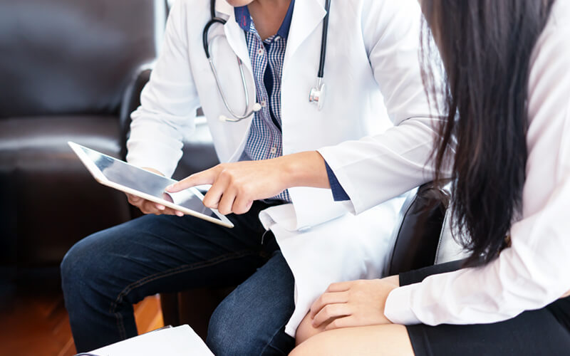 Doctors viewing patient data on tablet device