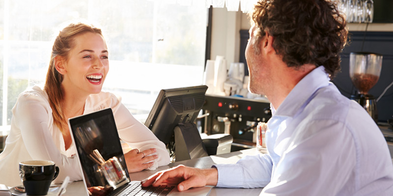 Waitress taking woman's order from POS system in cafe