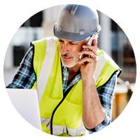 Construction worker on site in hard hat using mobile device and laptop