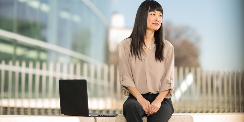 Young professional woman sitting outside with laptop