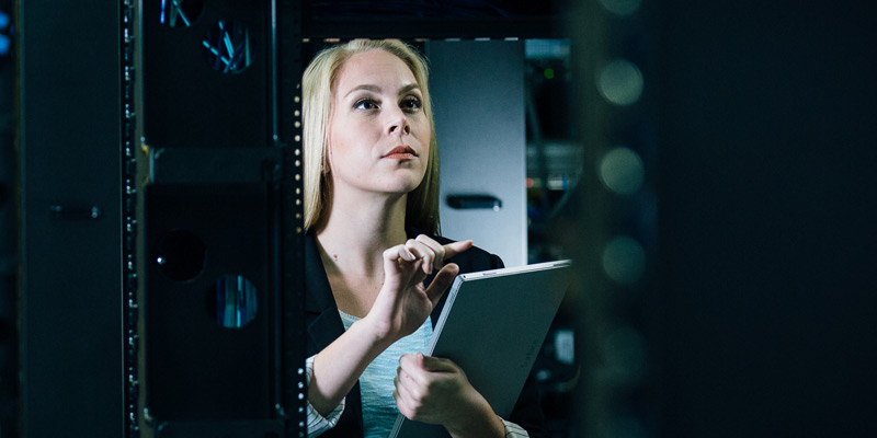 Business woman on tablet in server room