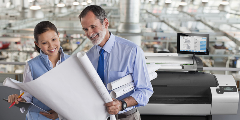 Businessman holds and shares large printed pages with woman