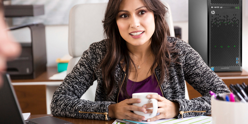 Smiling woman with coffee works in modern office