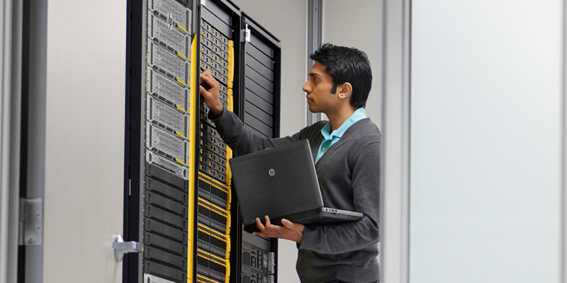 Man holding HP notebook in server room