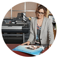 Business woman looks at print from HP Designjet T830 Multifunction Printer