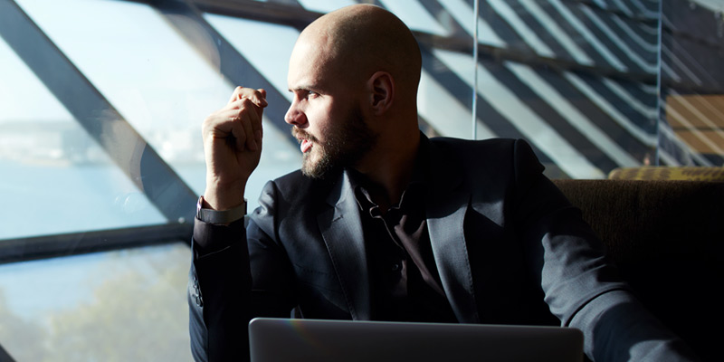 Businessman on laptop looking outside windows with sun shining in