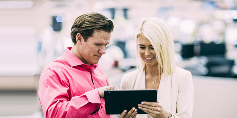 Smiling business woman shows man information on tablet