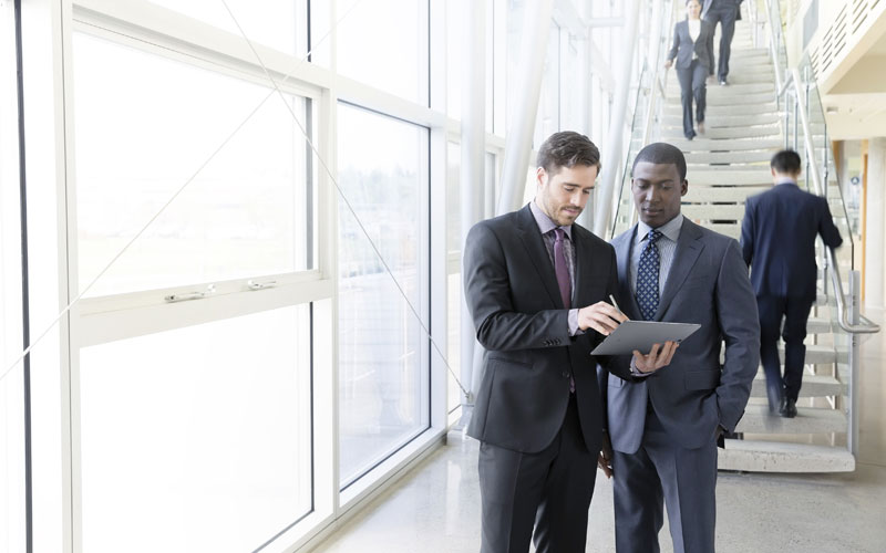 Two business men using tablet device while walking in building