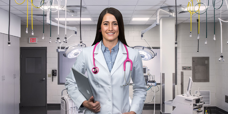 Smiling female doctor in labcoat stands in medical lab