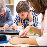 Three young schoolchildren working on tablet devices.
