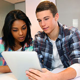 Young man and lady looking at laptop together.