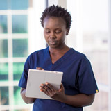 Woman in scrubs working on tablet