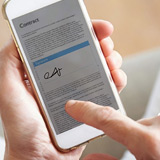Close up of finger applying e-signature using electronic signature software with smart phone