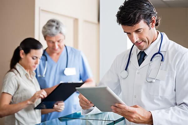 Doctor on tablet device in hospital
