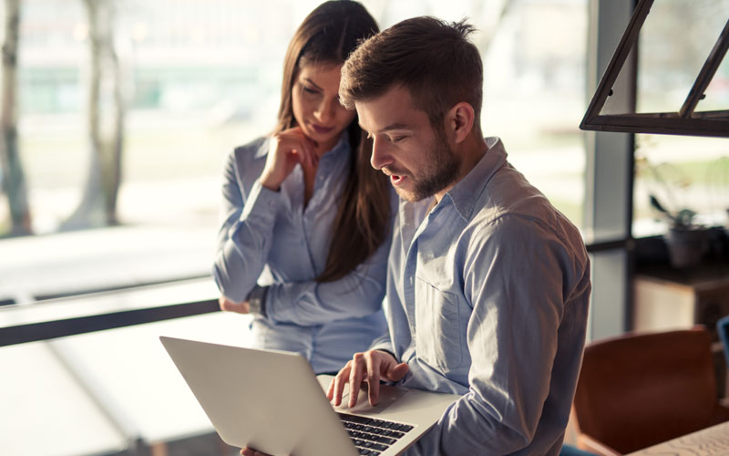 Man and woman looking over laptop device