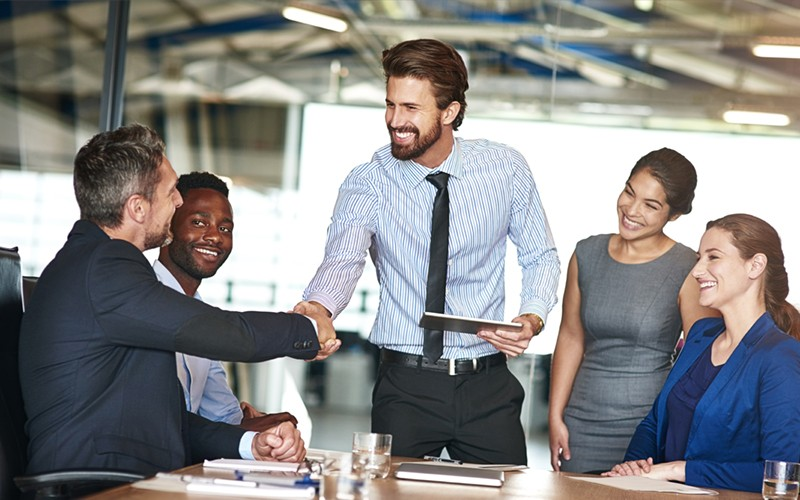 Woman smiles at round table with other business partners