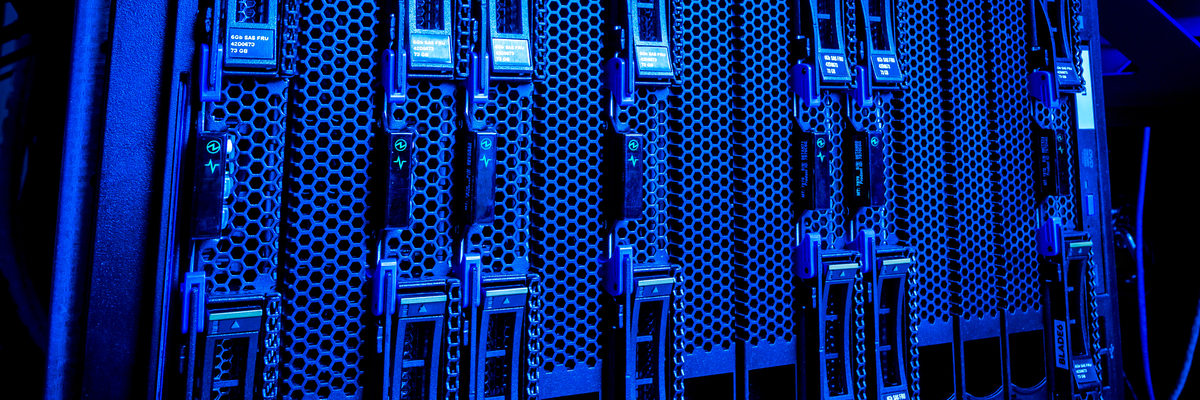Closeup of blue servers with lights blinking in data center.