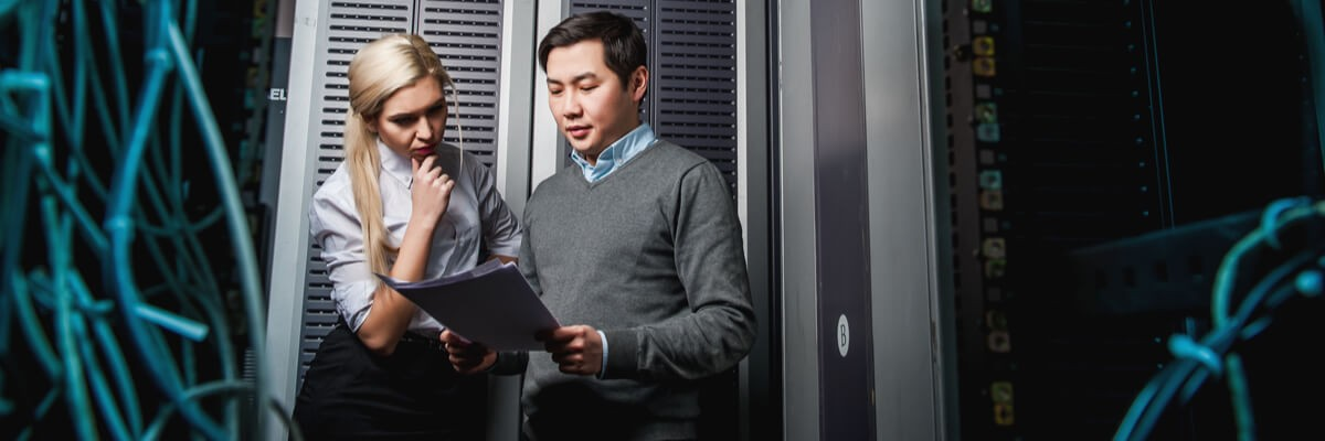 Woman and man standing in a server room, looking at files.