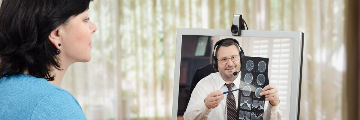 Doctor delivering telehealth services to a woman over video chat