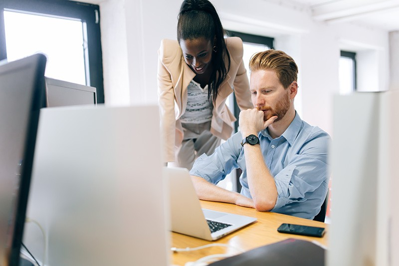 Business woman advising male colleague over desktop computer