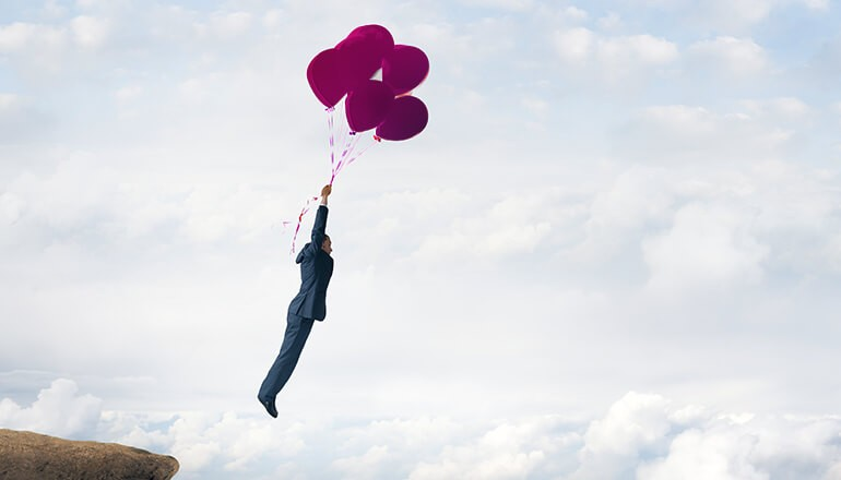 Conceptual image of a businessman holding on to balloons as he floats into clouds