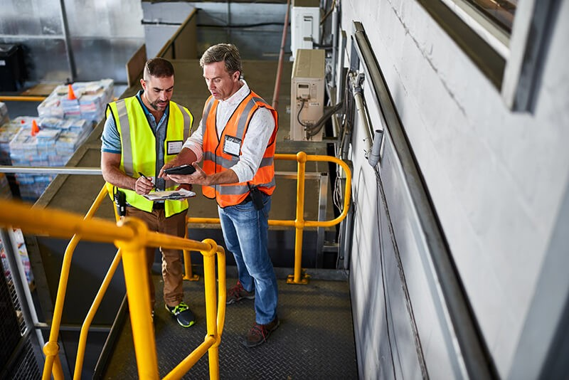 Two men on tablet device in manufacturing facility
