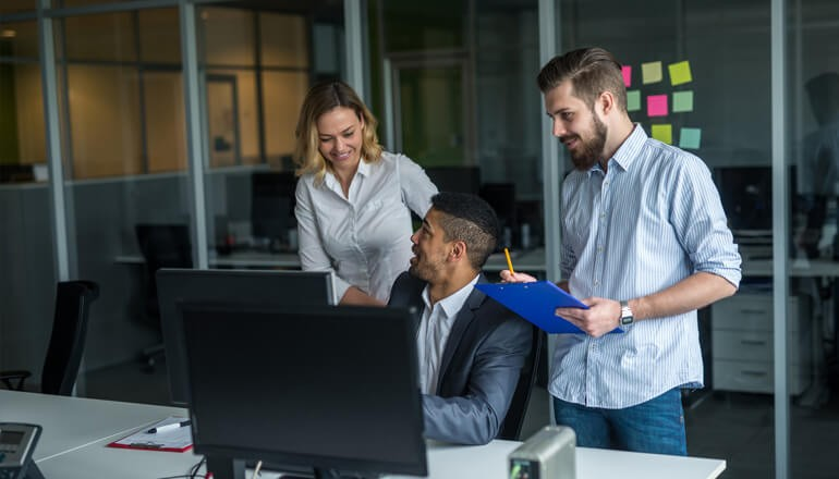 Three business employees collaborating in front of desktop