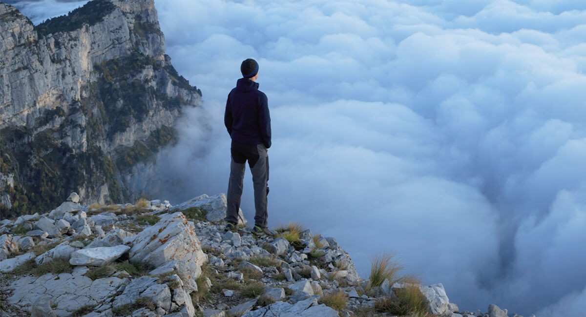 Man overlooking clouds at the peak of a mountain