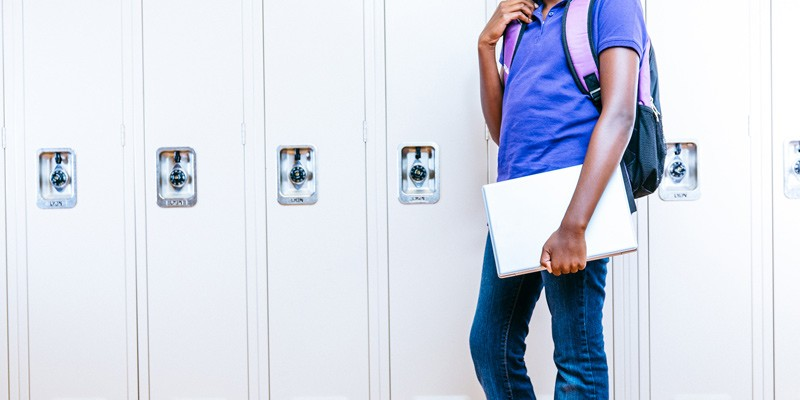 Female middle school student against lockers with chromebook notebook