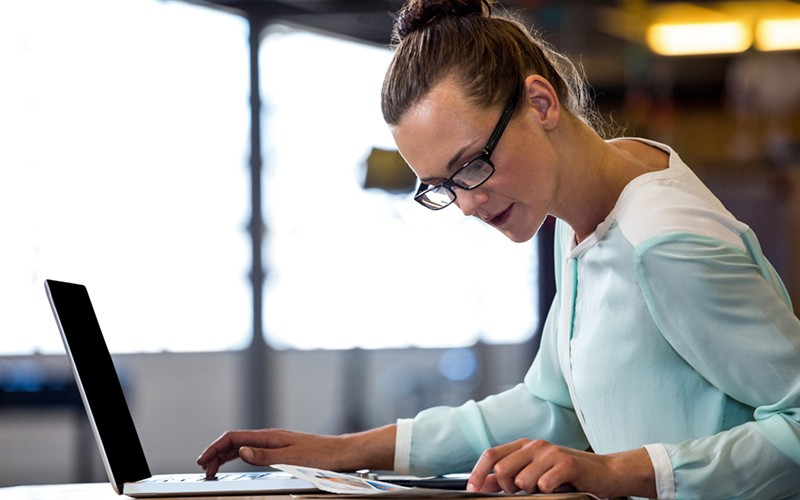 Female employee working on laptop and looking at document