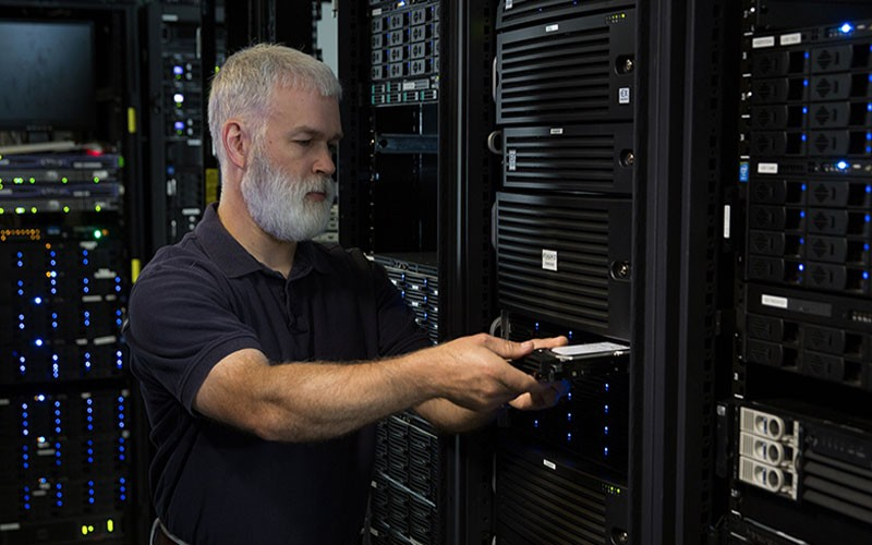 IT professional inserting disk on data storage