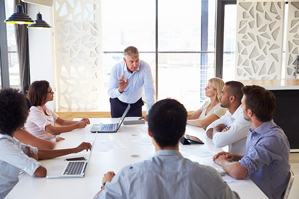 Businessman on laptop leads team meeting