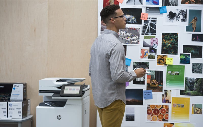 Business professional looking over prints made with HP Designjet Z5400 44 in PostScript ePrinter