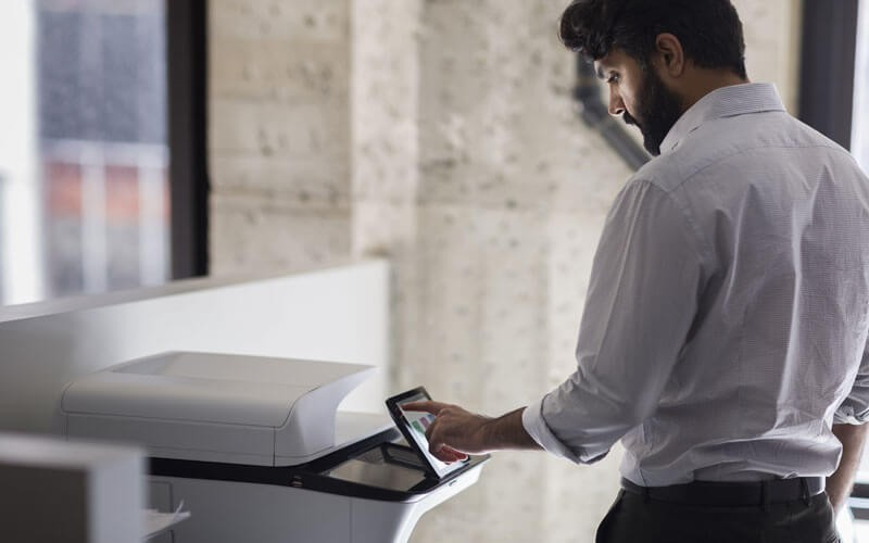 HP LaserJet Enterprise Flow MFP M527z at a print station in an office setting using an HP Pro Tablet 608 G1 to print color output
