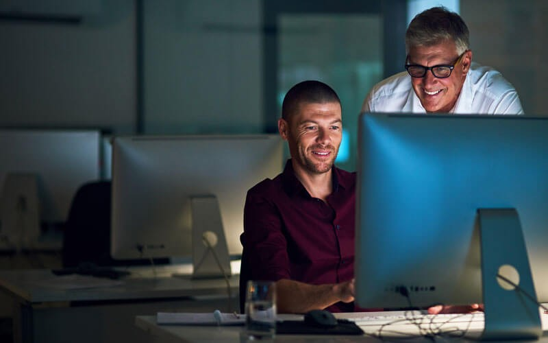 Two men smiling while working on monitor
