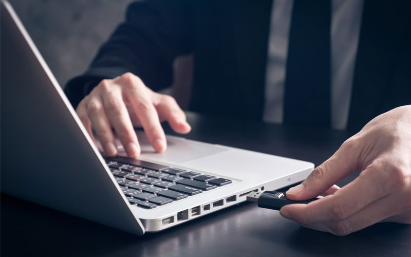 Business man using USB drive in laptop device