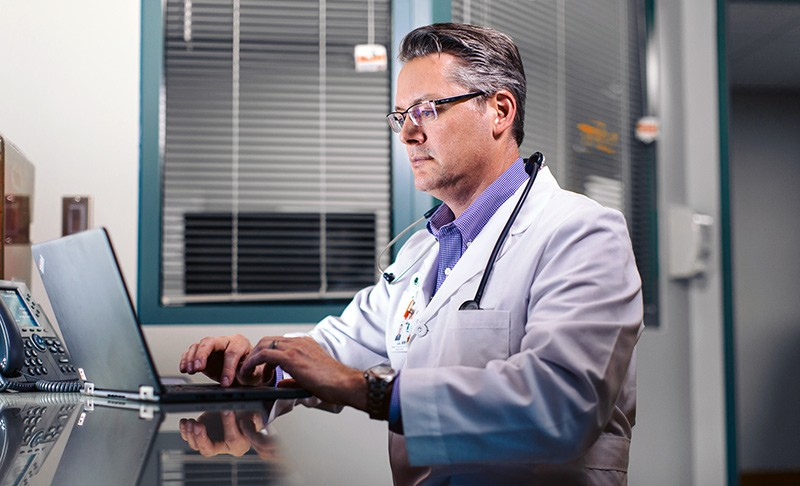 Doctor on notebook computer in office