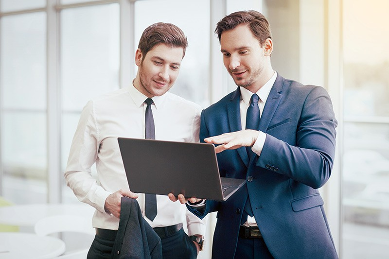Two males looking at black laptop