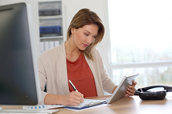 Business woman using tablet computer at her office desk