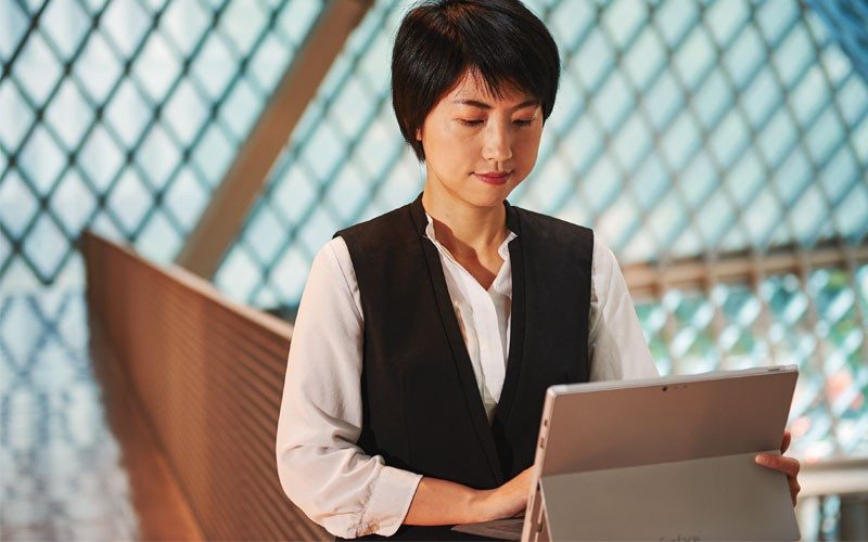 Woman working on Microsoft device