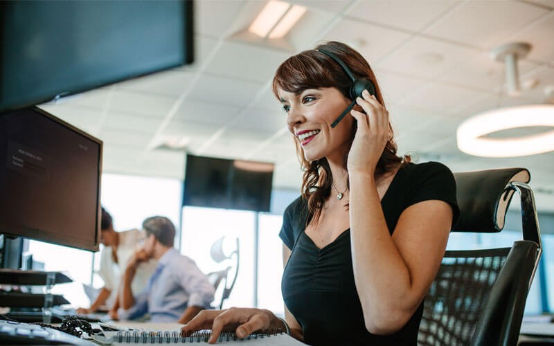 Smiling call center representative with headset in office