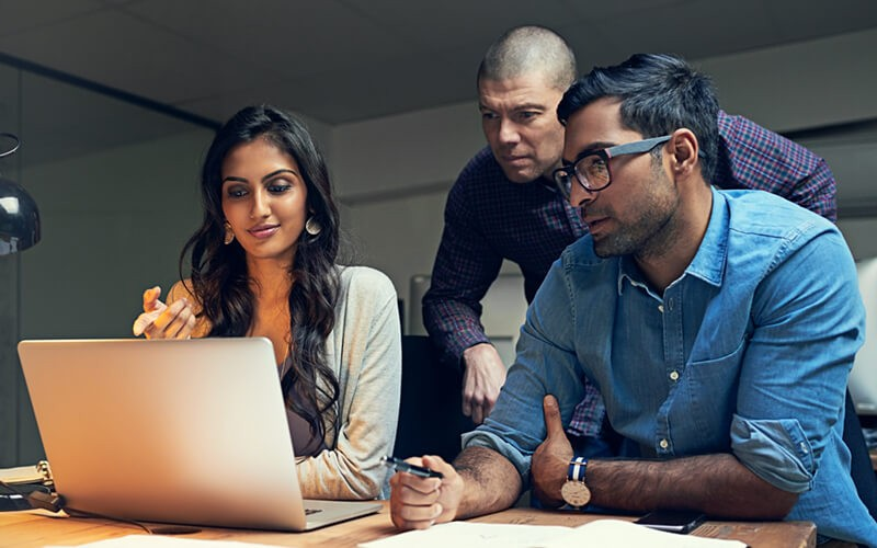 Three business employees working on laptop