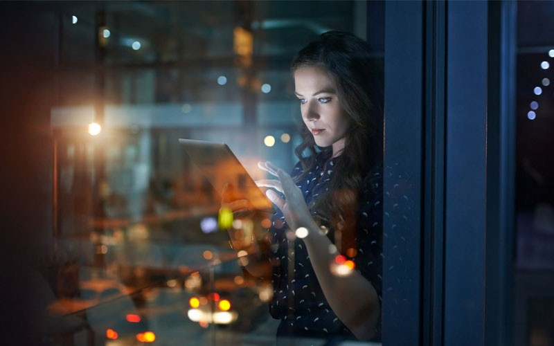 Woman using touch screen device in open office late at night