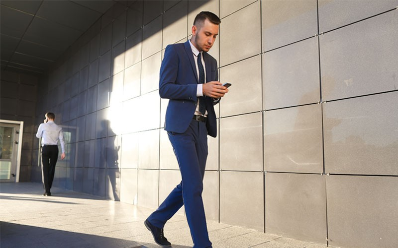 Business man walking outside while texting on mobile phone