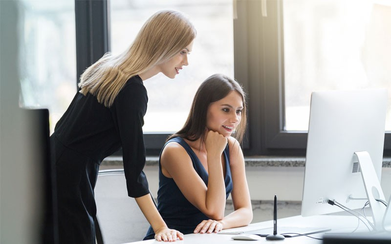 Two woman looking over monitor and desktop