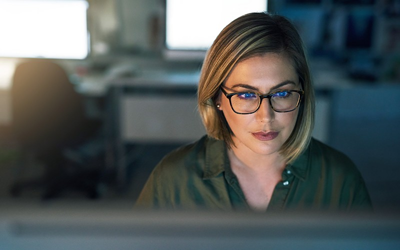 Businesswoman in glasses reviews security assessment on computer
