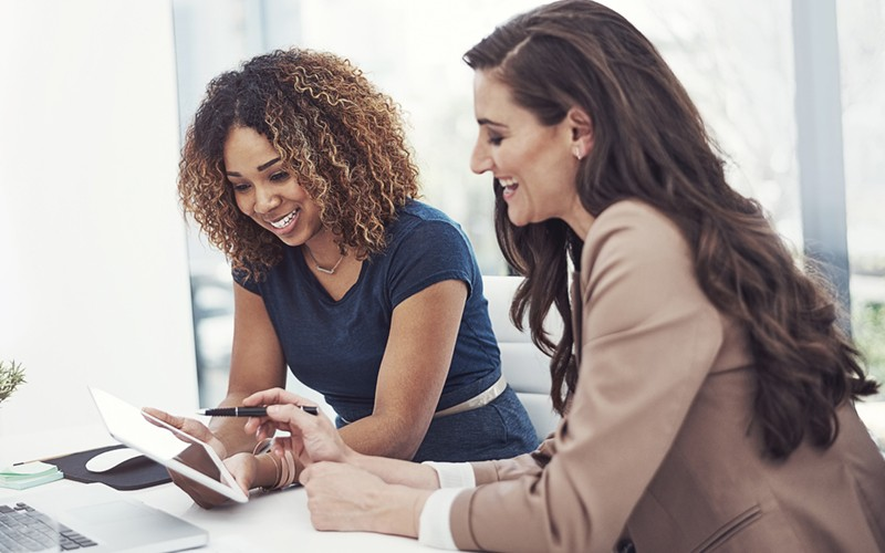 Businesswomen on tablet device thinking up new strategy